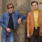 Brad Pitt and Leonardo DiCaprio lean up against a wall with their heads leaning to the side in the movie Once Upon a Time... In Hollywood