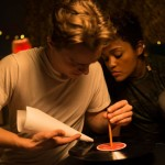 Lauren 'Lolo' Spencer and Chris Galust make a paper airplane in the movie Give Me Liberty