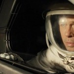 In a spacesuit Brad Pitt looks out the window of a spacecraft in the movie Ad Astra