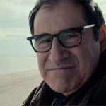 Richard Kind smiling on a beach in the movie Auggie