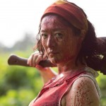 A bloodied woman holding a hatchet behind her head in the movie Cut of the Dead