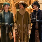 Some of the ladies of Downton Abbey stand dressed up and ready to go out in the Downton Abbey movie