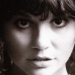 A black and white photo of singer Linda Ronstadt looking into the camera