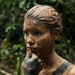 A female child soldier has mud spread on her face in the movie Monos