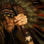 Sheri Moon Zombie wearing an Indian headdress and holding a bow in 3 From Hell