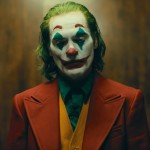 Joaquin Phoenix in the movie Joker in full clown makeup and a suit waiting in an elevator