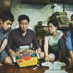 A family huddles together folding pizza boxes in Bong Joon Ho's film Parasite