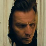 Ewan MacGregor peers through an axe hole in a door in the movie Doctor Sleep