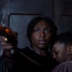 Cynthia Erivo holds a child and points a pistol at the camera in the movie Harriet