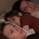 Scarlett Johansson and Adam Driver lay in bed with their son in the movie Marriage Story