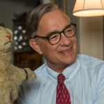 Tom Hanks as Mr. Rogers holding his puppet Daniel the Tiger in the movie A Beautiful Day in the Neighborhood