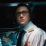 Joseph Gordon-Levitt sitting in a plan cockpit with a bloody arm looking behind him in the movie 7500