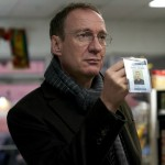 David Thewlis in the movie Guest of Honour holding a badge in a convenience store