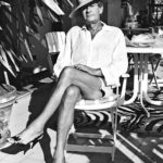 In a black and white photo the photographer Helmut Newton sits with his legs crossed in a chair outdoors