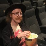 Oscar Goff sitting at a movie theatre with popcorn in his hand