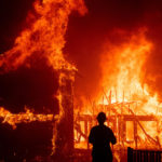 A firefighter standing in the shadows of a massive blaze in the documentary Rebuilding Paradise