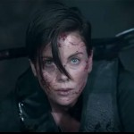 Charlize Theron crouches with hair in her face and an axe on her back in the movie The Old Guard