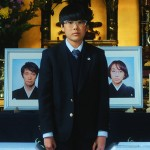 Keita Ninomiya looks sad standing in front of photos of his parents in the movie We Are Little Zombies