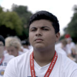 A boy wearing a Texas lanyard sitting in a large group of boys in the documentary Boys State