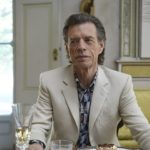 Mick Jagger dressed in cream colored blazer in the movie The Burnt Orange Heresy