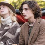 Elle Fanning and Timothée Chalamet sit together in the movie A Rainy Day in New York