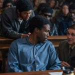 Yahya Abdul-Mateen II leans over to talk to Mark Rylance in the movie The Trial of the Chicago 7