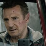 Liam Neeson looks a little roughed up sitting in his car with a cellphone in his hand in the movie Honest Thief