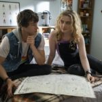 Kyle Allen and Kathryn Newton sit on a bed together looking at a map in the movie The Map of Tiny Perfect Things